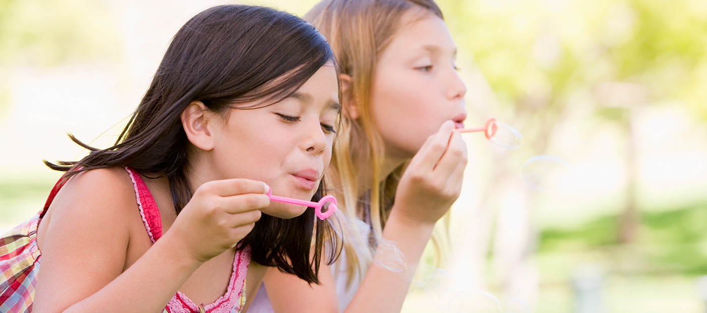 2 girls blowing soap bubbles